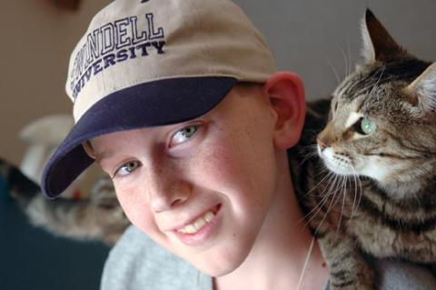This boy and his family are fostering this sweet brown tabby cat.