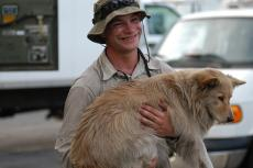 Ethan carrying a tan colored dog after rescuing him following a hurricane