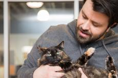 Man cradling a tortoiseshell colored cat in his arms