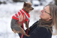 Woman holding a terrier dog wearing a red sweater