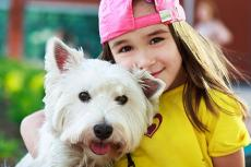 Little girl with pink hat hugging a terrier