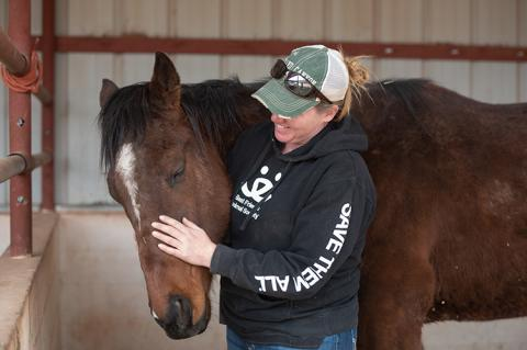 Woman wearing a long-sleeve Best Friends shirt cradling a horse's head in a stall