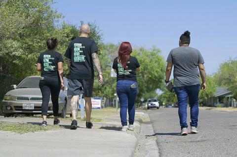 The backs of four people as they are advocating for animals in a neighborhood